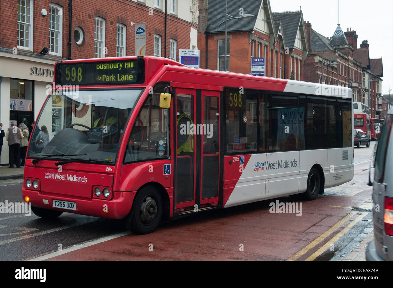 An Optare Solo operated by National Express West Midlands pulls away from a bus stop in Wolverhampton - Stock Image