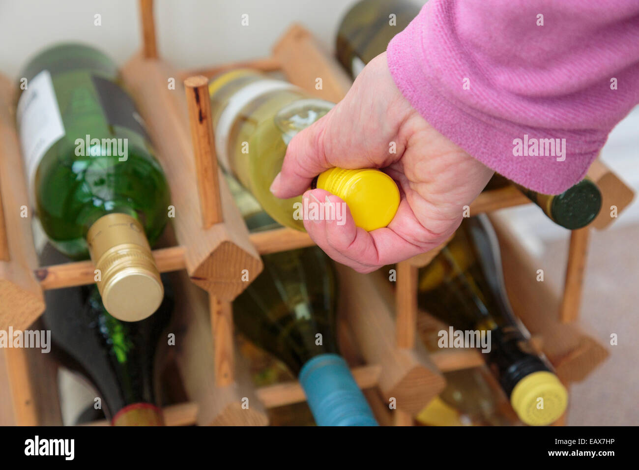 Everyday scene where a woman chooses a bottle of white wine to drink from a wine rack at home. Lifestyle concept. - Stock Image