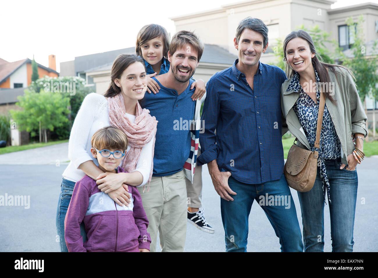 Family posing together on suburban street, portrait - Stock Image