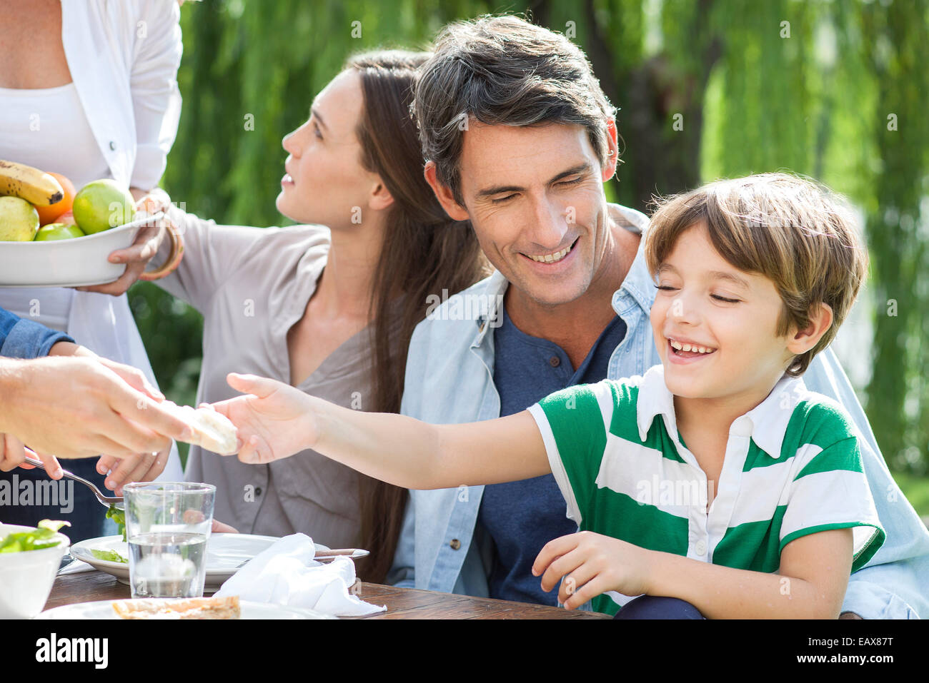 Family eating healthy meal together outdoors, father holding son on lap - Stock Image