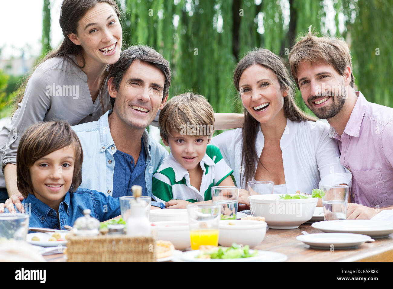 Family posing for portrait at outdoor gathering - Stock Image