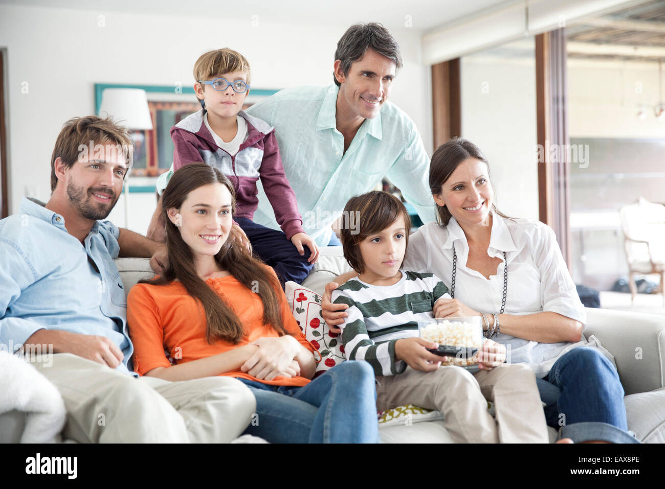 Extended family watching TV together - Stock Image