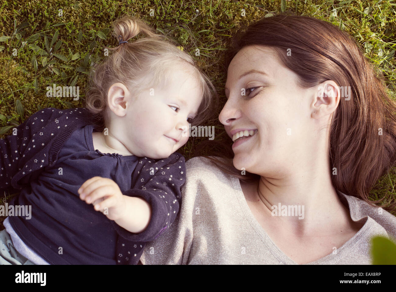 Mother and baby girl lying on grass, smiling at each other - Stock Image