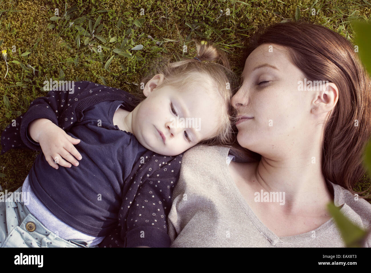 Mother and baby girl napping on grass Stock Photo