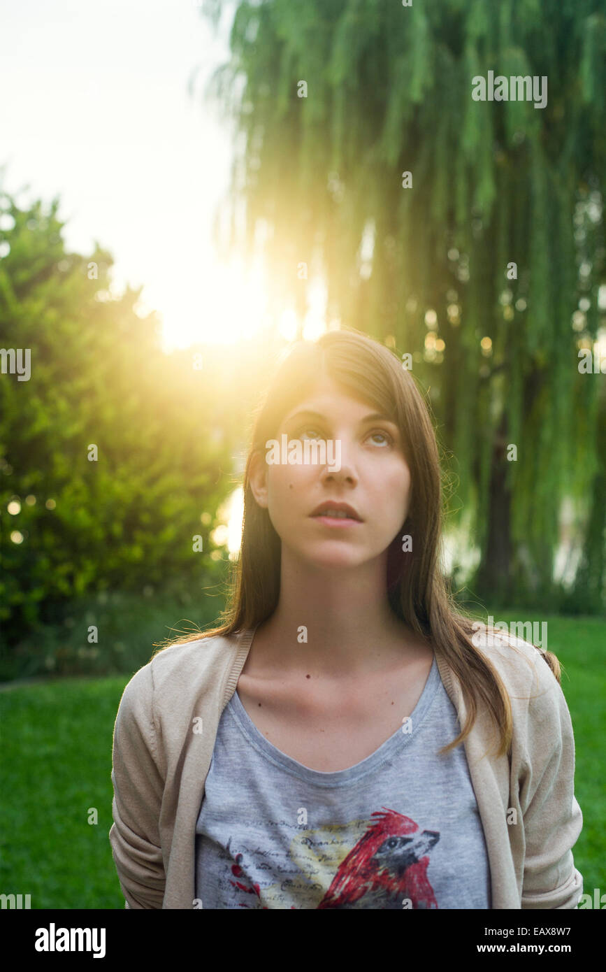 Woman walking in park appreciating beauty in nature - Stock Image
