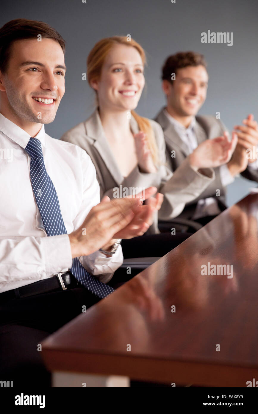 Young business professionals applauding at conclusion of presentation - Stock Image