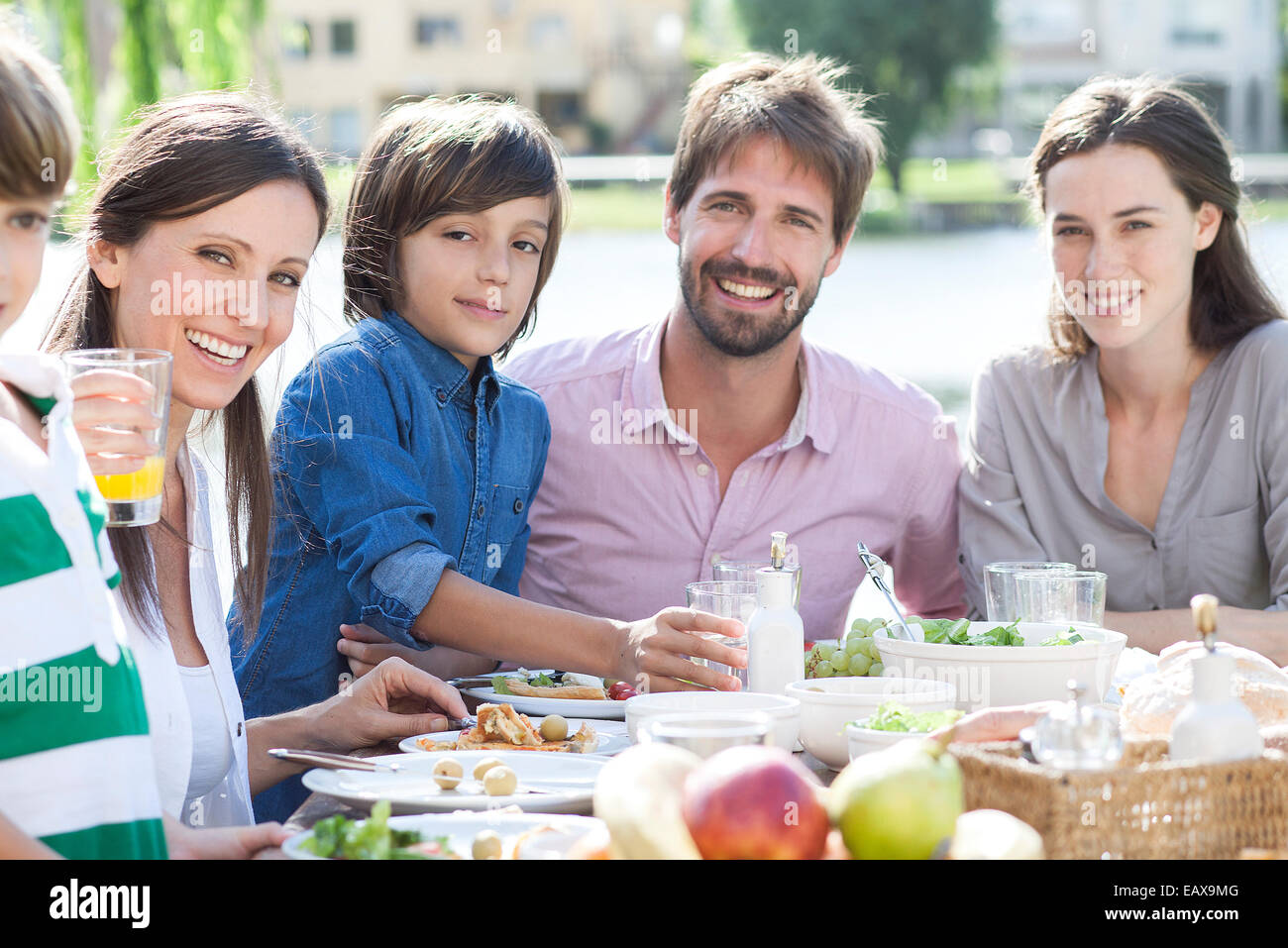 Family eating together outdoors, portrait - Stock Image