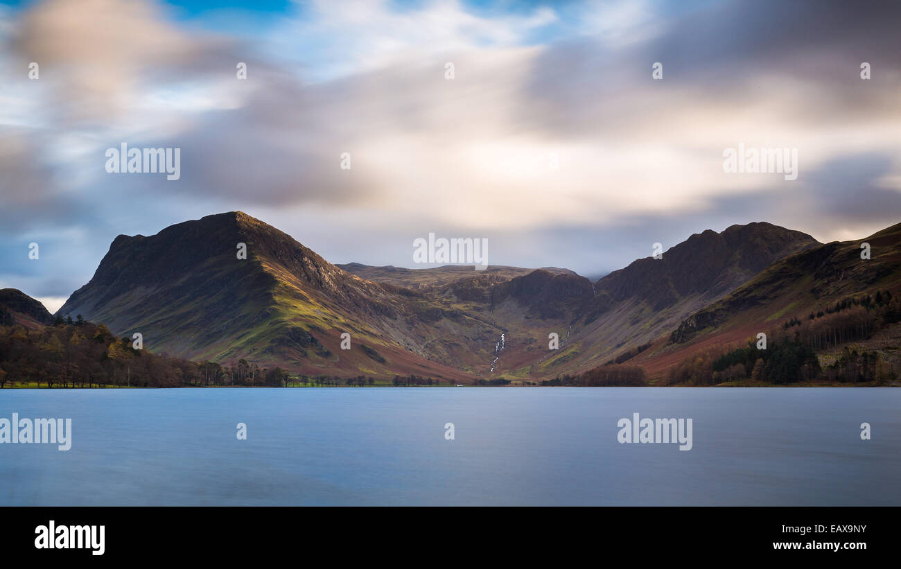 A glimmer of sunlight on the fells of Fleetwith Pike, across Buttermere in the Lake District National Park, England - Stock Image