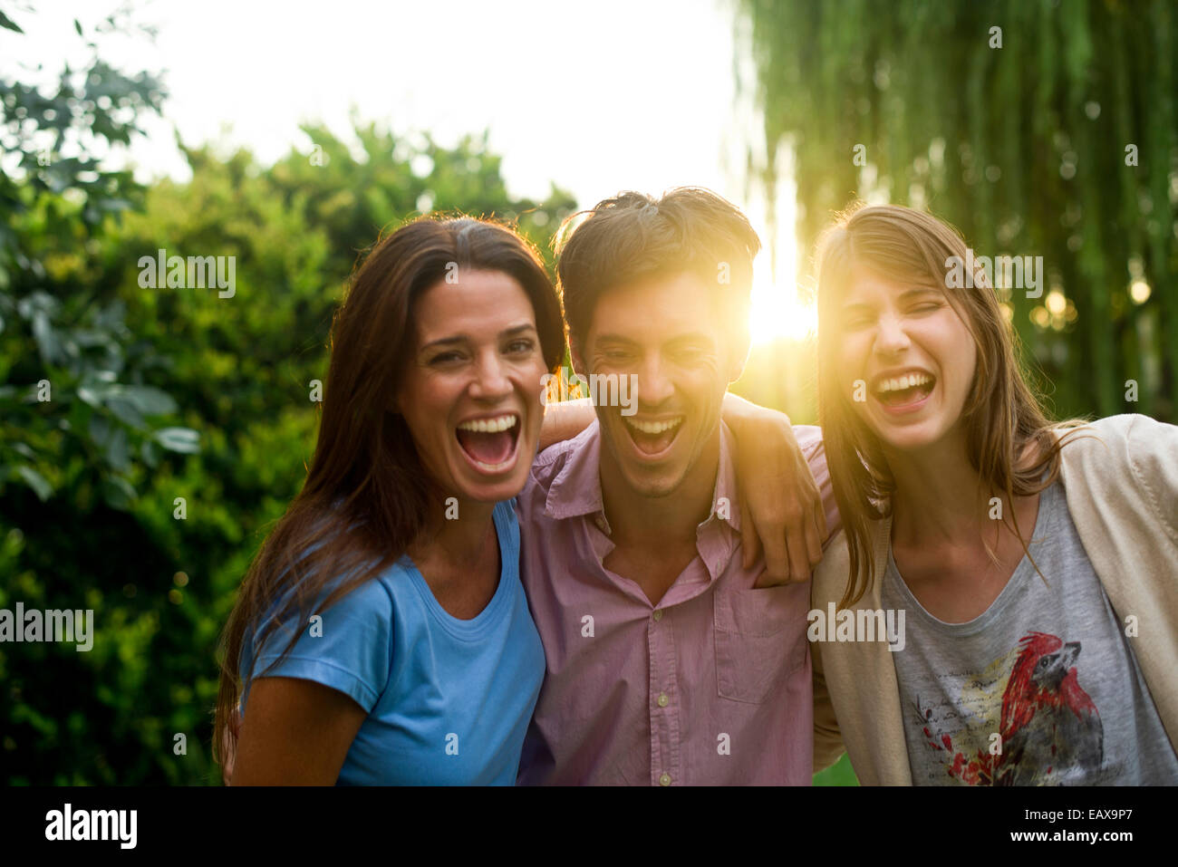 College friends having laughs together in park - Stock Image
