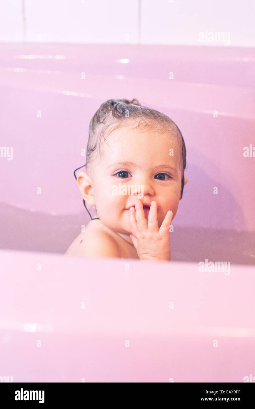 Baby girl taking a bath - Stock Image