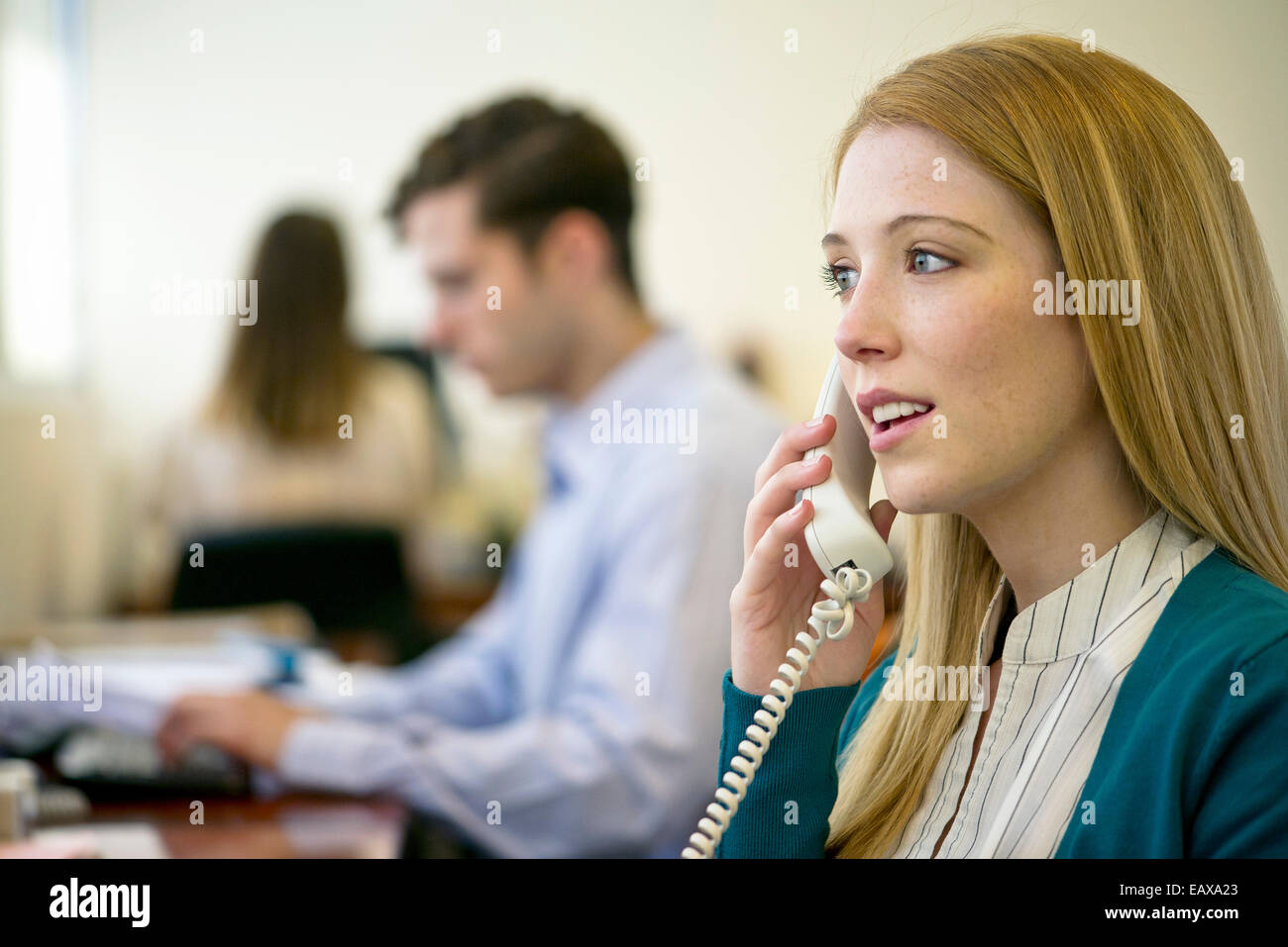 Woman using landline phone in office Stock Photo