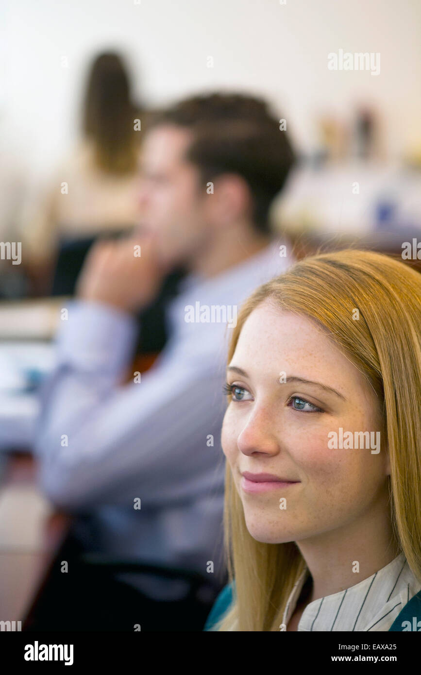 Young woman smiling dreamily in office - Stock Image
