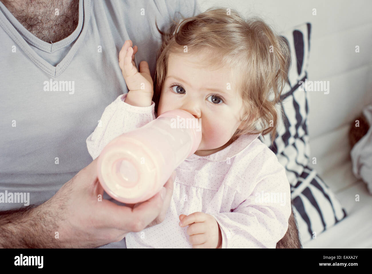 Baby girl sitting on father's lap, drinking from bottle, cropped - Stock Image
