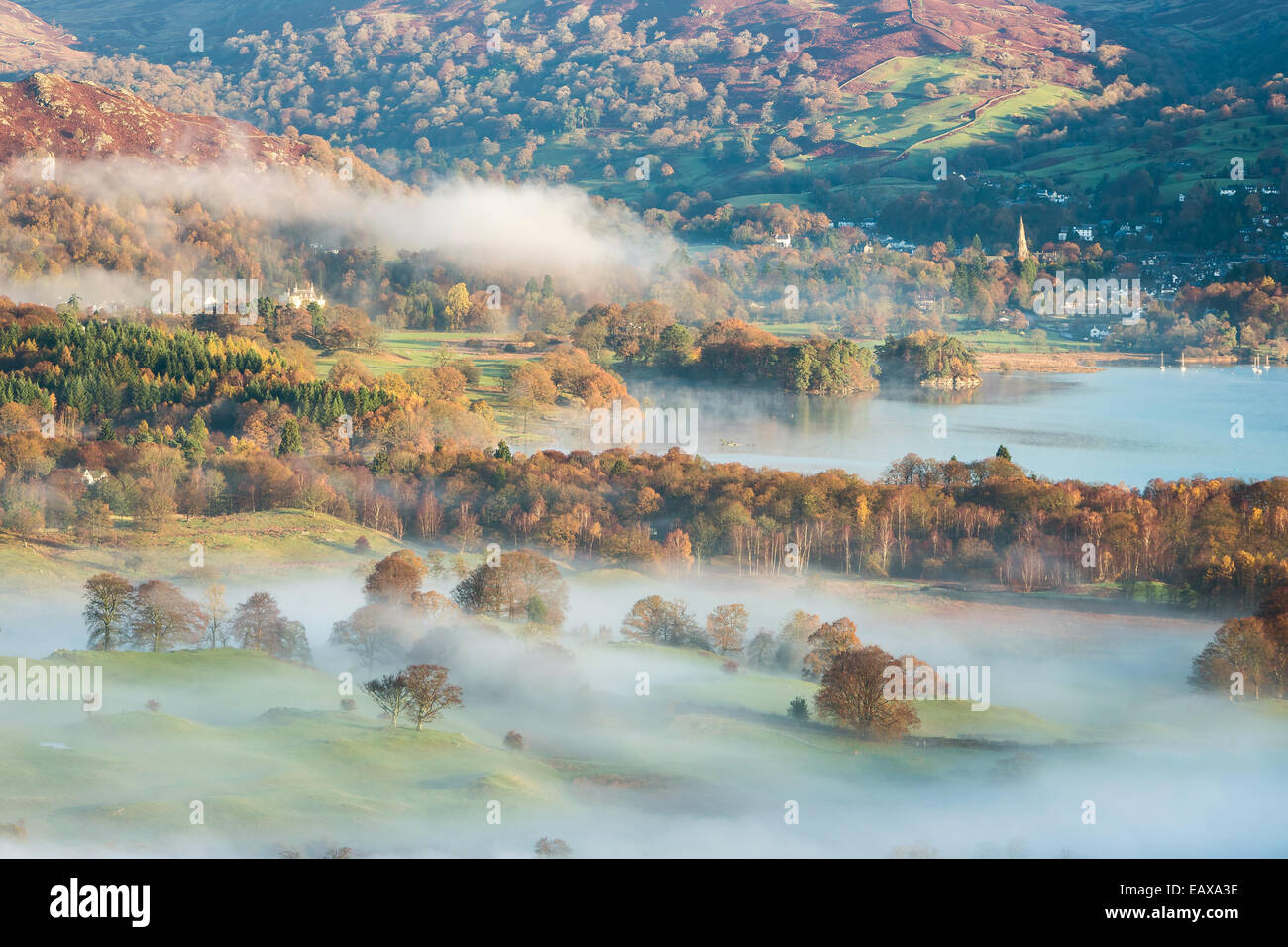 Hanging mists across the autumnal countryside looking towards Ambleside and the northern end of Lake Windermere - Stock Image