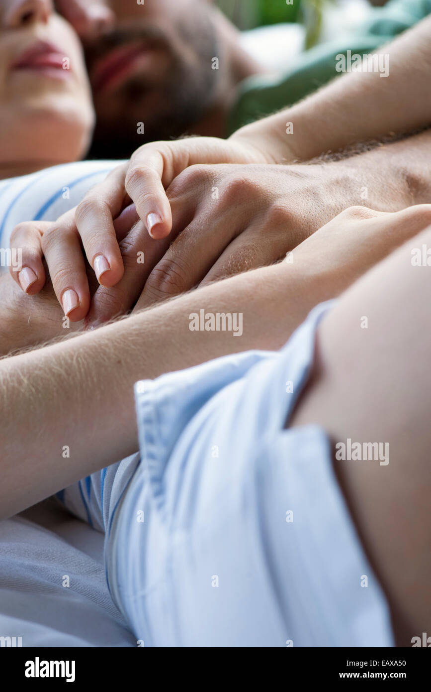 Couple reclining together, holding hands - Stock Image