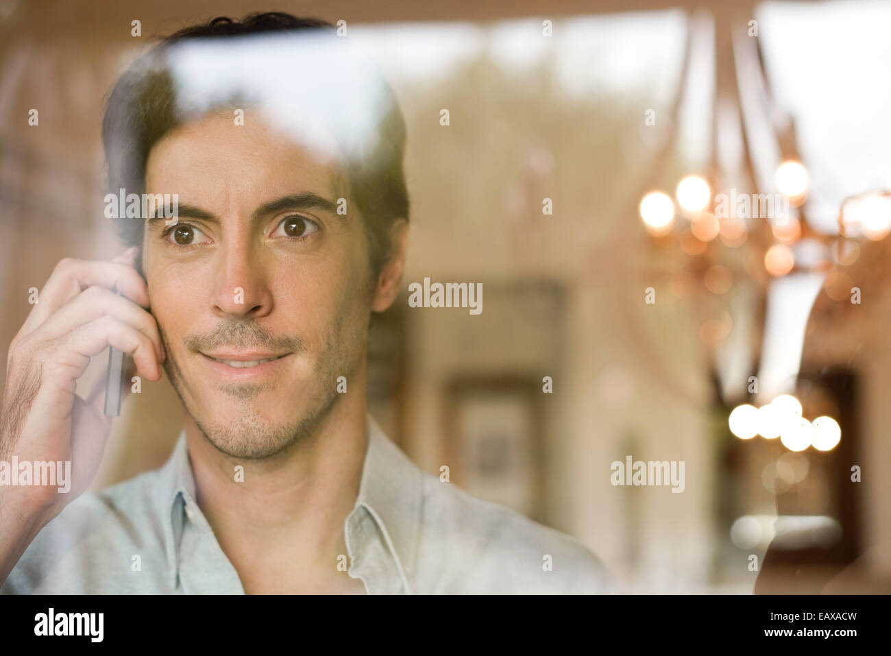 Man using cell phone looking out window - Stock Image