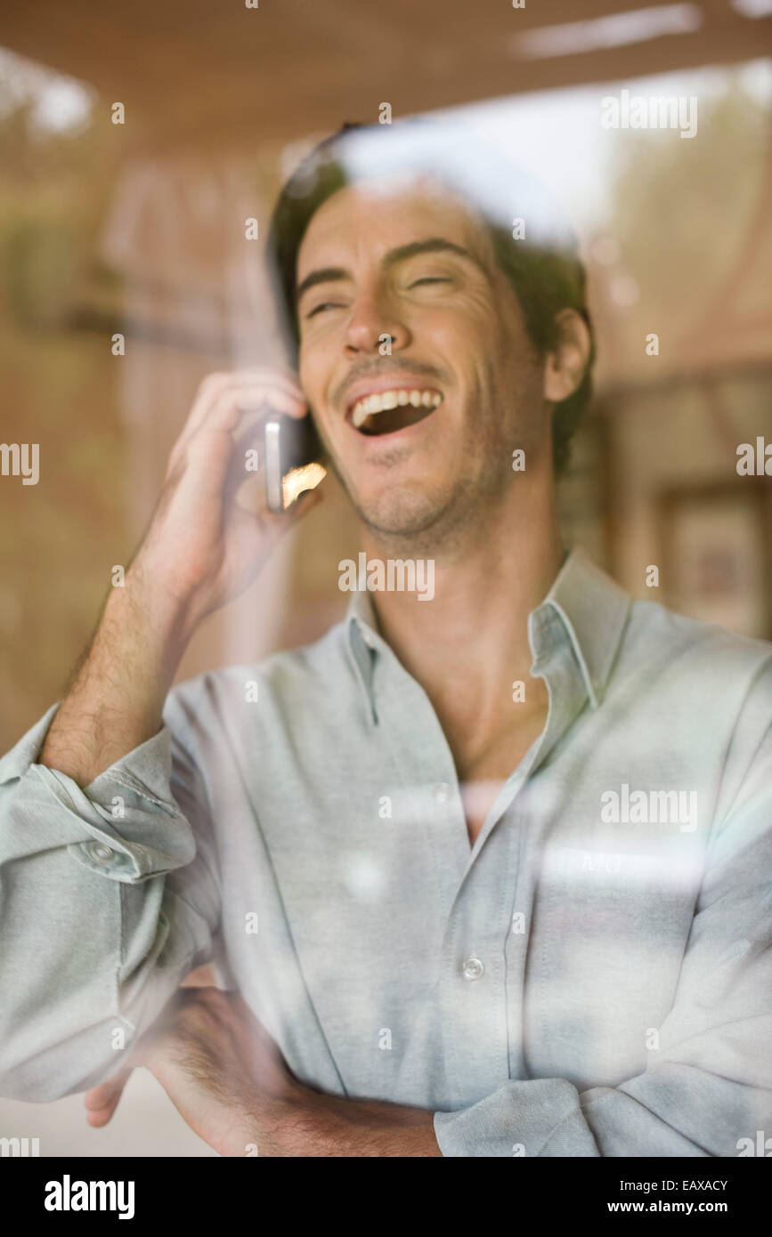 Man using cell phone bursting out laughing - Stock Image