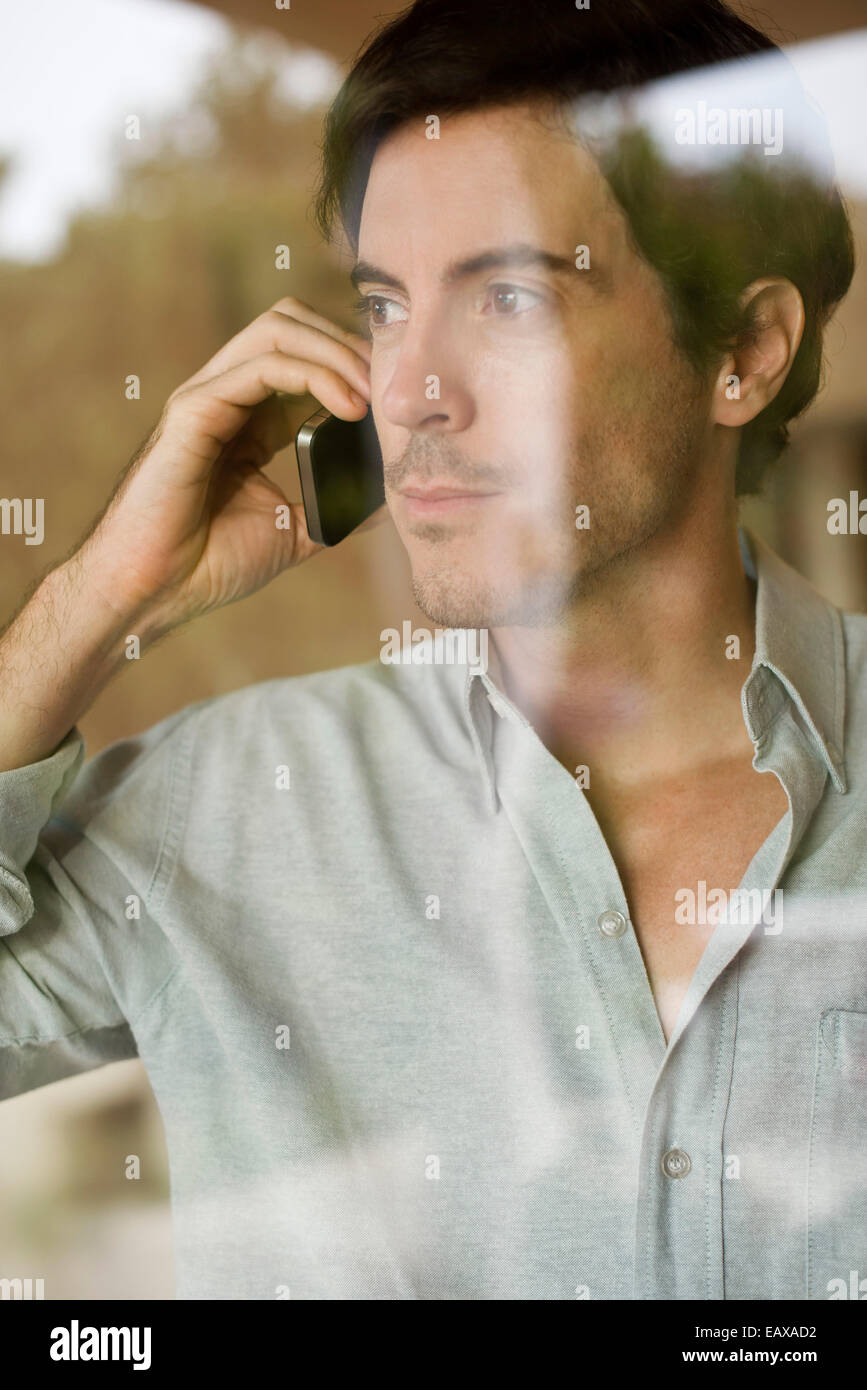 Man using cell phone looking out window Stock Photo