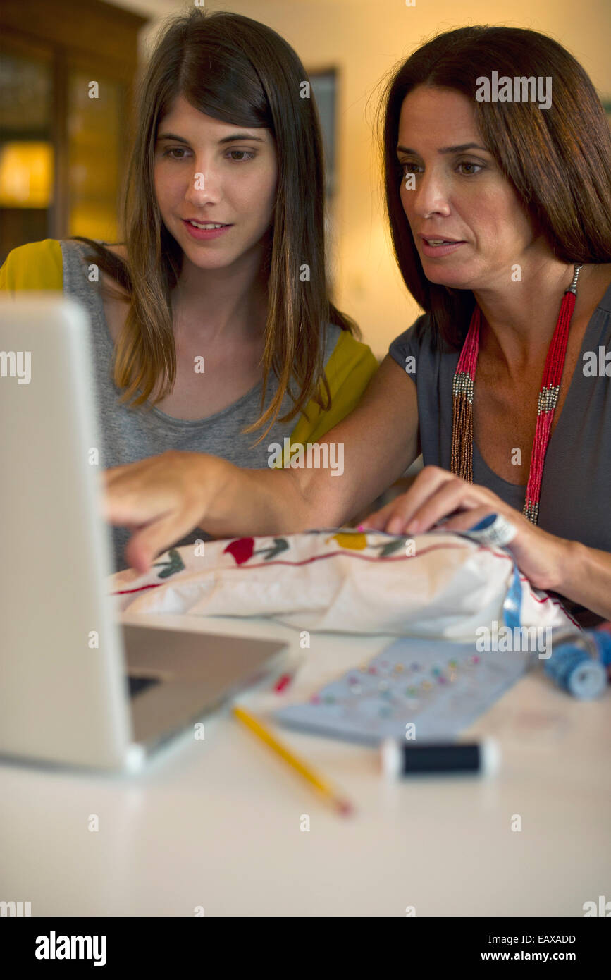 Mother and daughter learning embroidery together by watching online videos - Stock Image