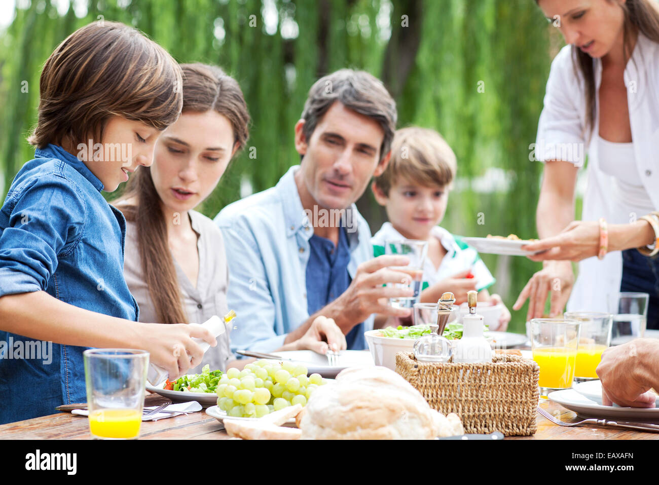 Family eating together at outdoor gathering - Stock Image