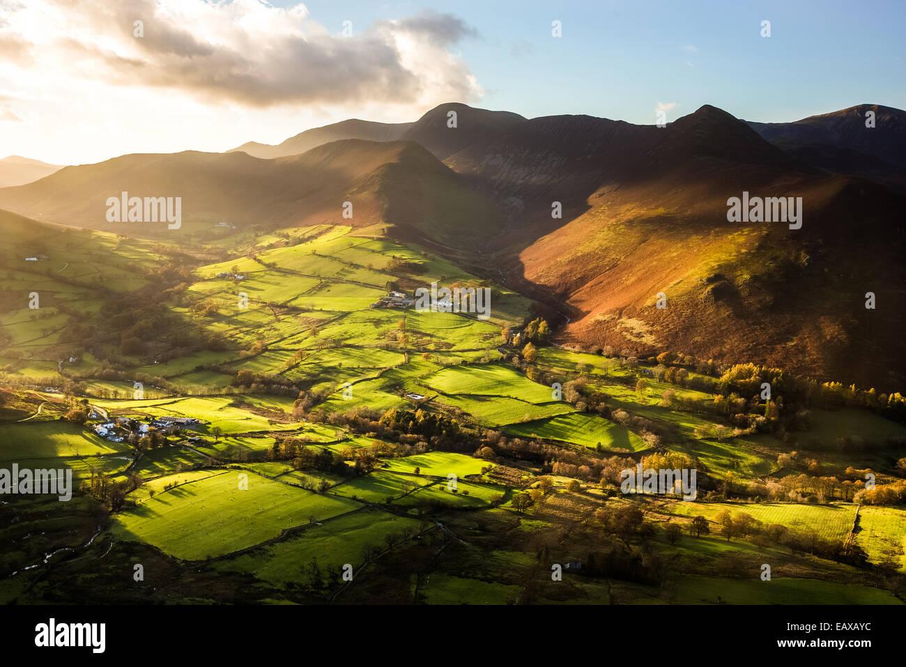 Striking autumnal sunlight illuminates the Newlands Valley viewed from the summit of Cat Bells near Derwent Water. - Stock Image