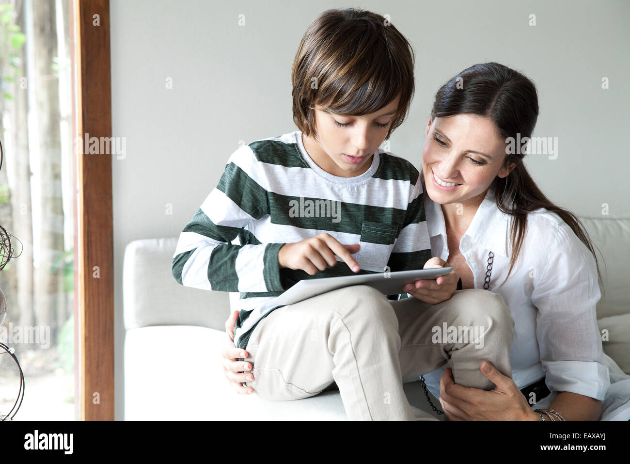 Mother and son using digital tablet together - Stock Image