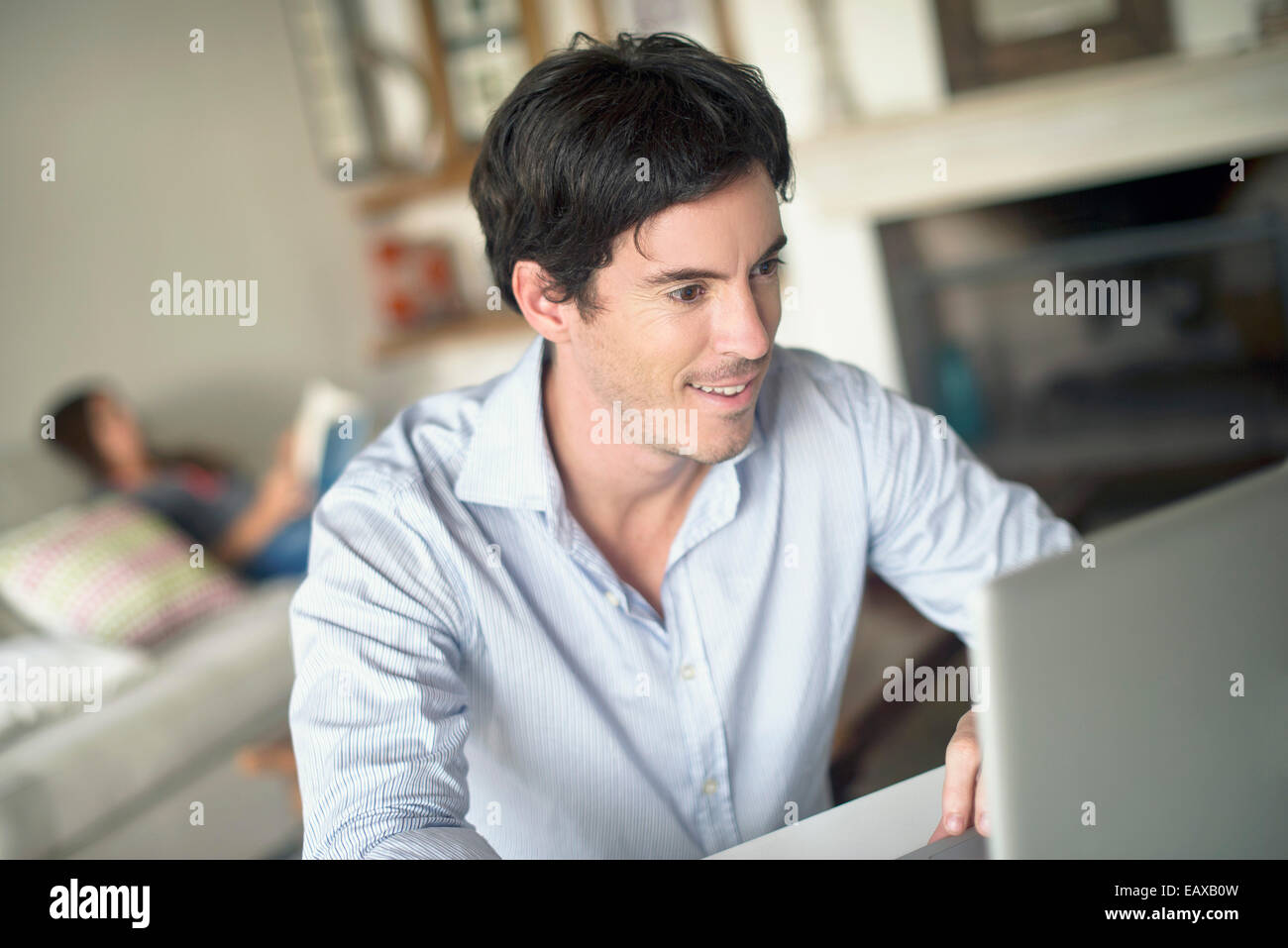 Man using laptop computer in living room - Stock Image