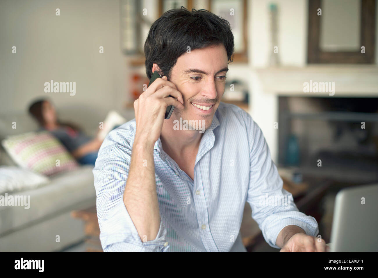Man talking on cell phone while using laptop computer - Stock Image