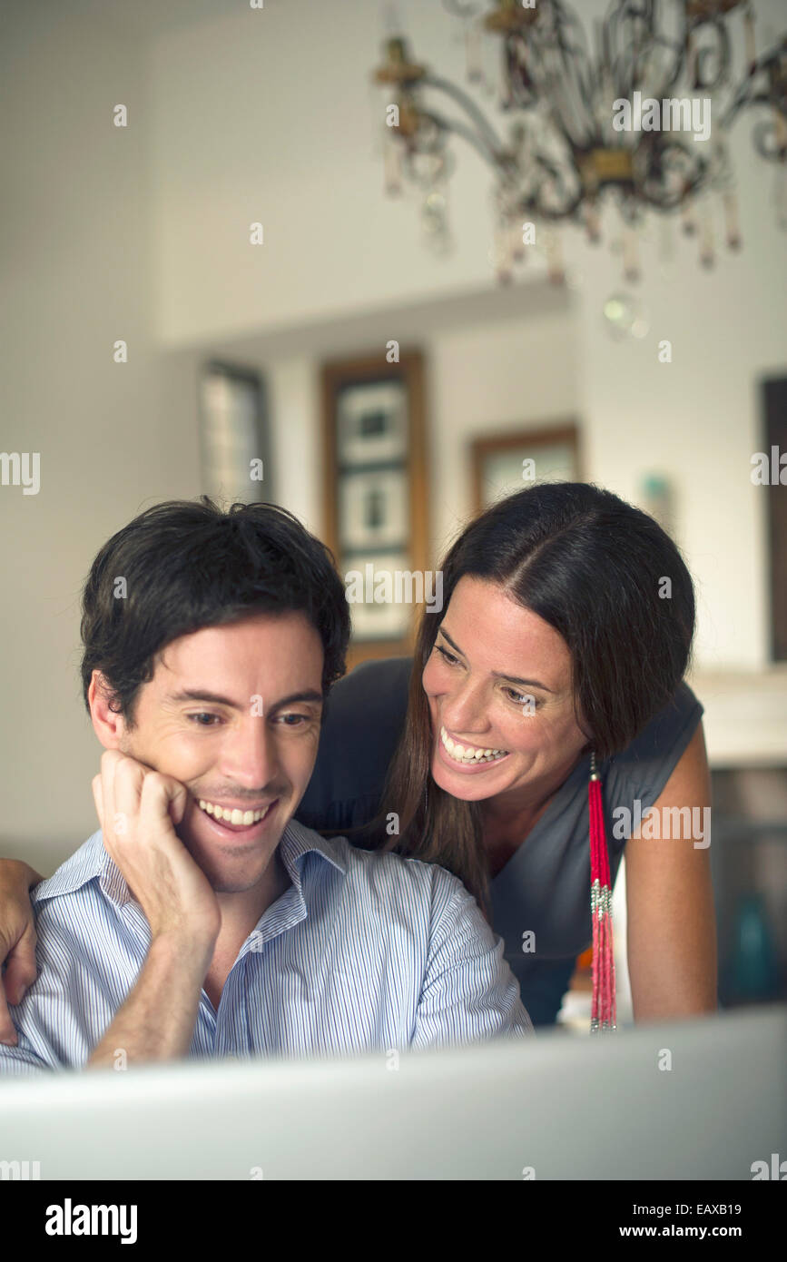Couple looking at laptop computer smiling - Stock Image
