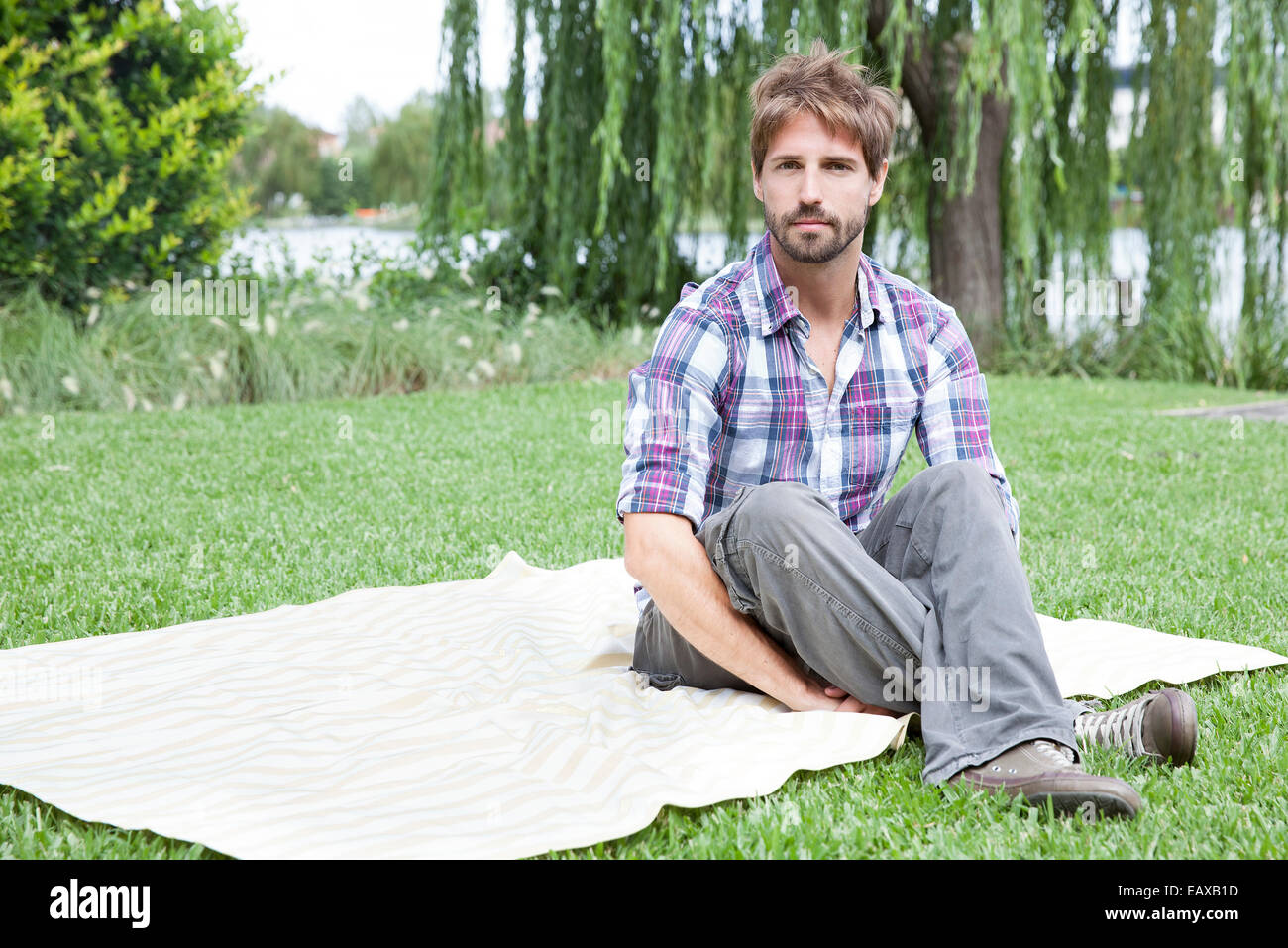 Man sitting on blanket outdoors - Stock Image