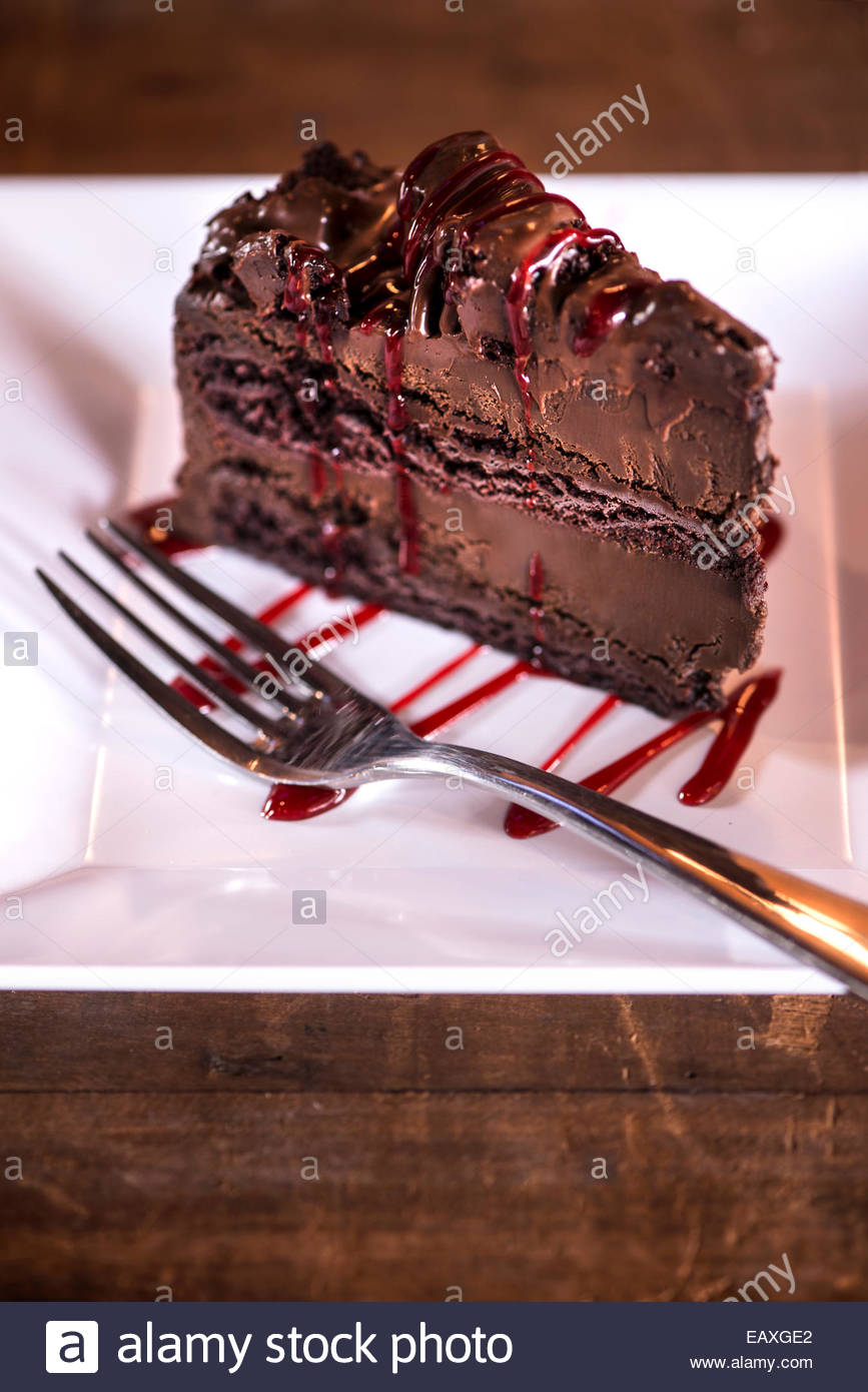 Large slice of chocolate cake with raspberry drizzle on white plate and rustic wood surface. & Large slice of chocolate cake with raspberry drizzle on white plate ...