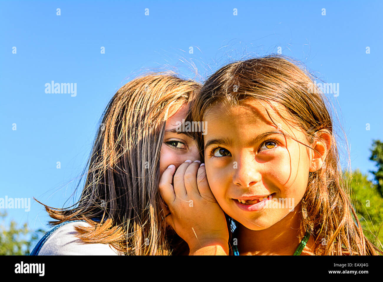 Two little girls are playing and whispering secrets in the park - Stock Image