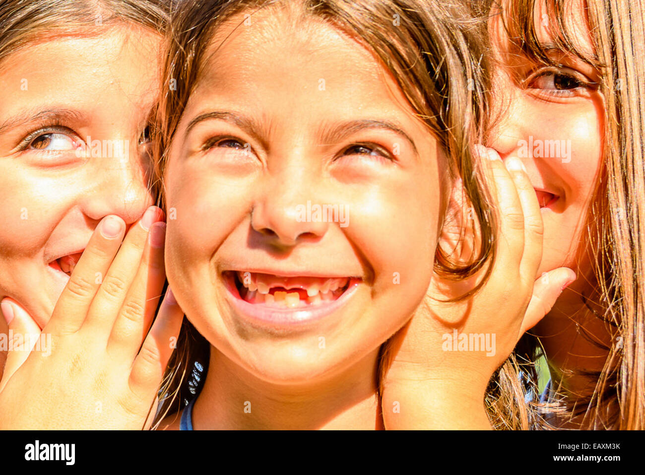 Three little girls  playing and whispering secrets in the park - Stock Image