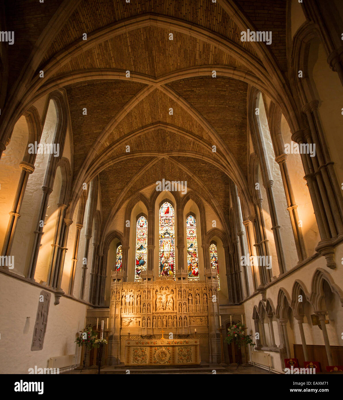 Interior of 11th century Brecon cathedral showing high nave with vaulted ceiling, stained glass windows & carved - Stock Image