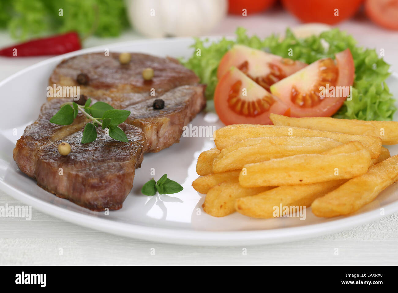 Pork chop steak cutlet meat meal with fries, vegetables and lettuce on plate - Stock Image