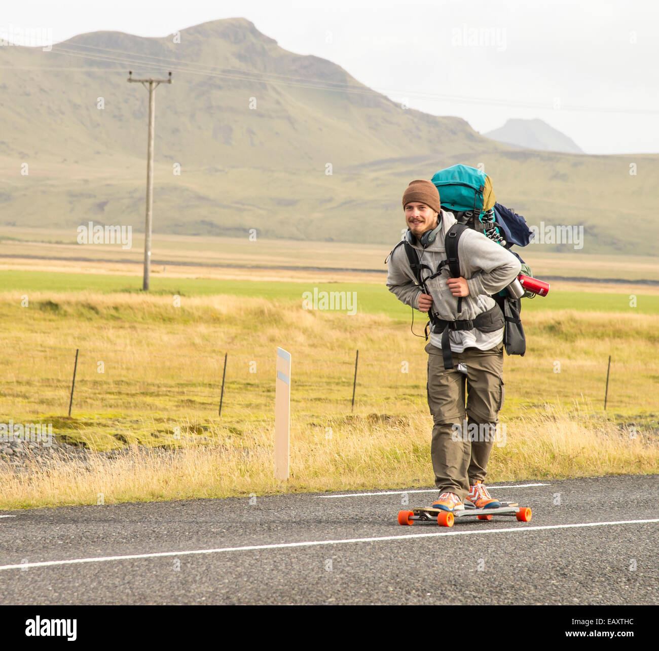 SkateBoarder on a long board with backpack on the Ring Road, Highway 1, Iceland - Stock Image