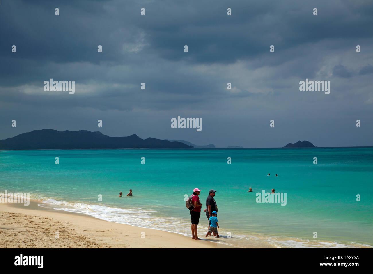 People swimming at Waimanalo Beach, and storm clouds, Oahu, Hawaii, USA - Stock Image