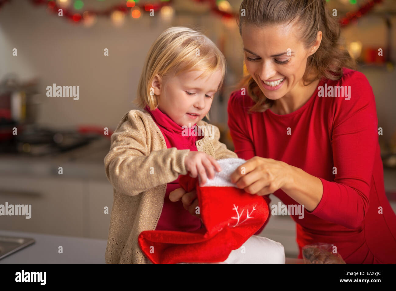 portrait of happy mother and baby with christmas stocking in kitchen