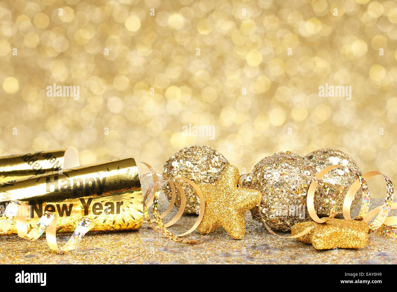 new years eve border of confetti and golden decorations on a twinkling gold