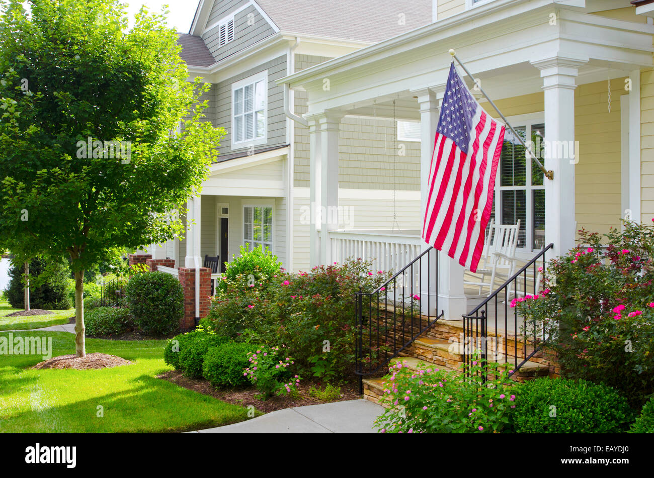 An American Flag Hangs From A Front Porch In A