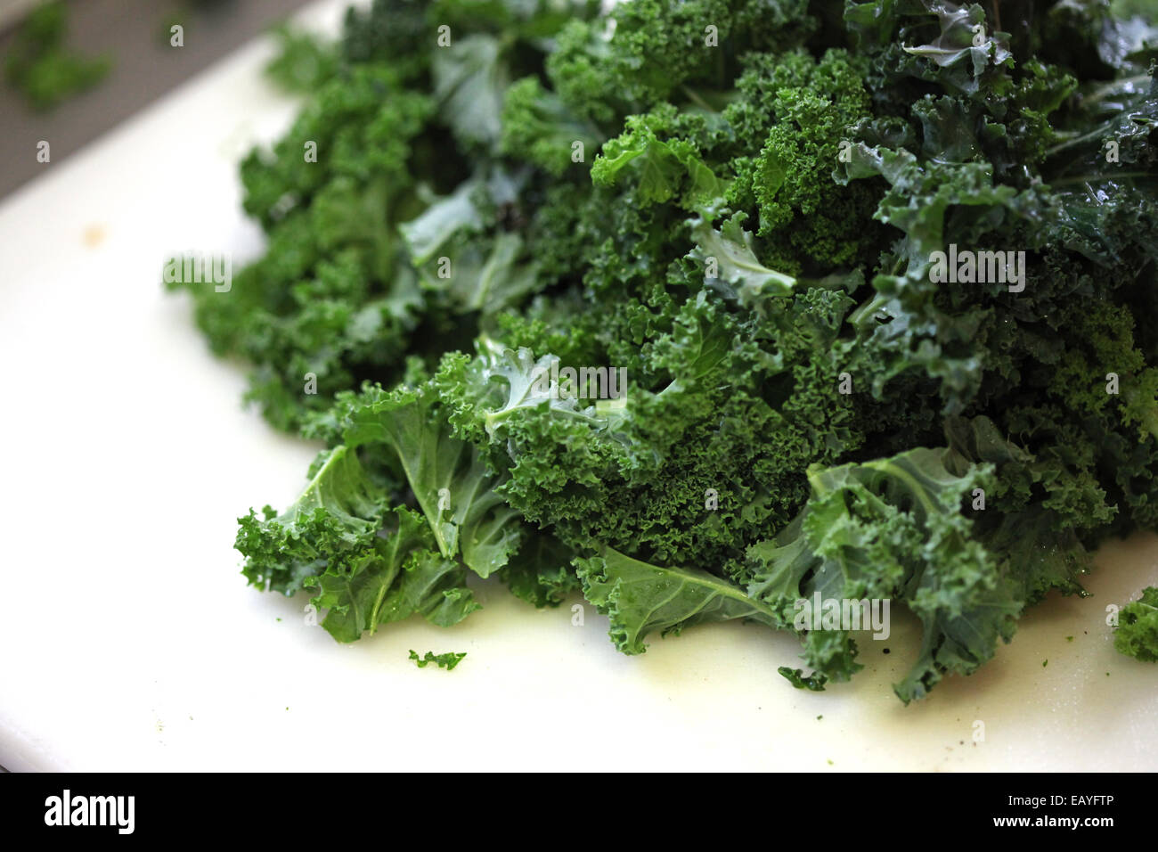 Close-up of prepared curly kale on a cutting board for a meal - Stock Image