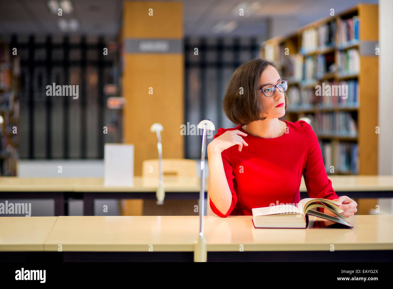 Young woman with glasses in library looking left - Stock Image