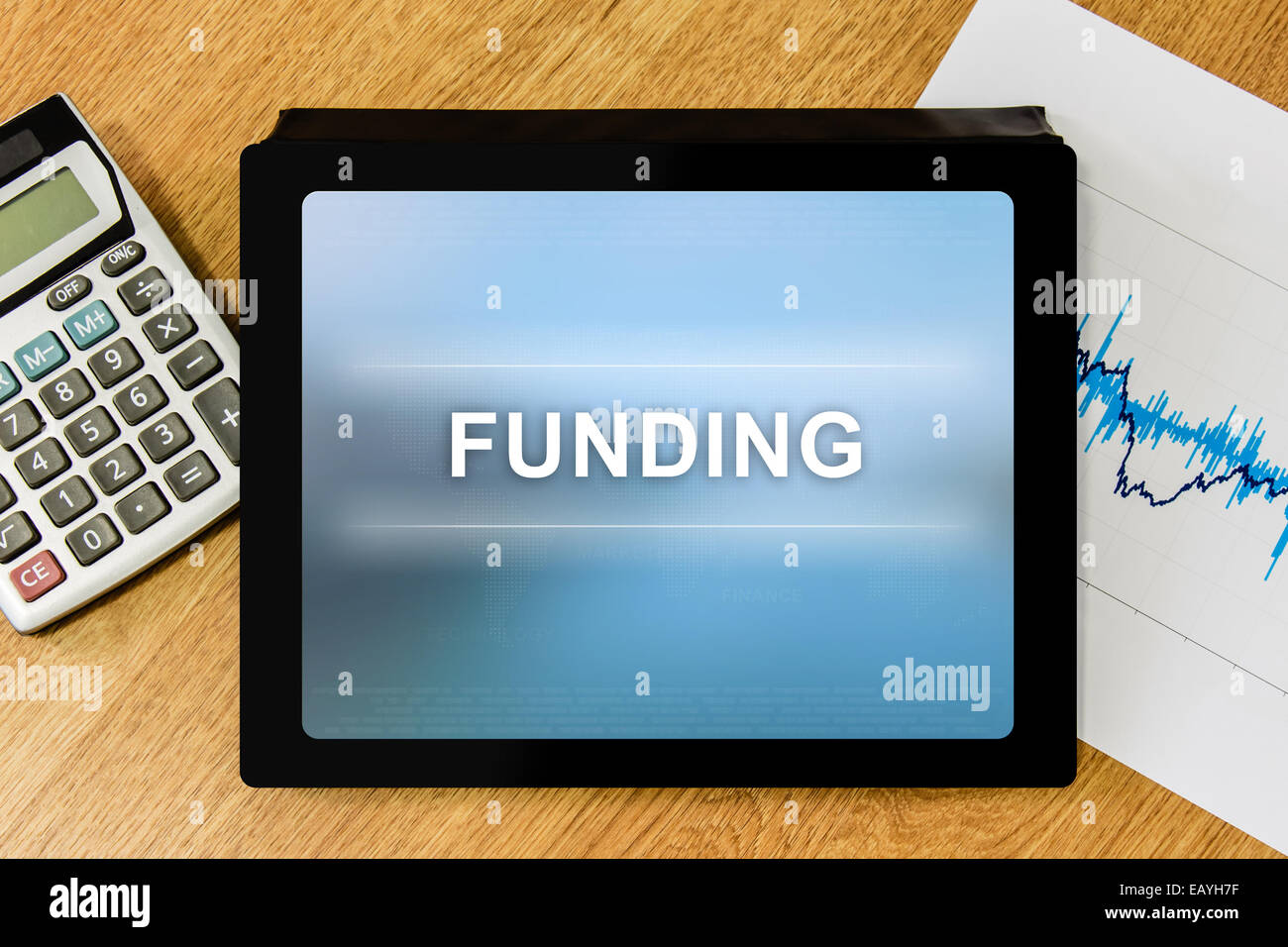 funding word on digital tablet with calculator and financial graph Stock Photo