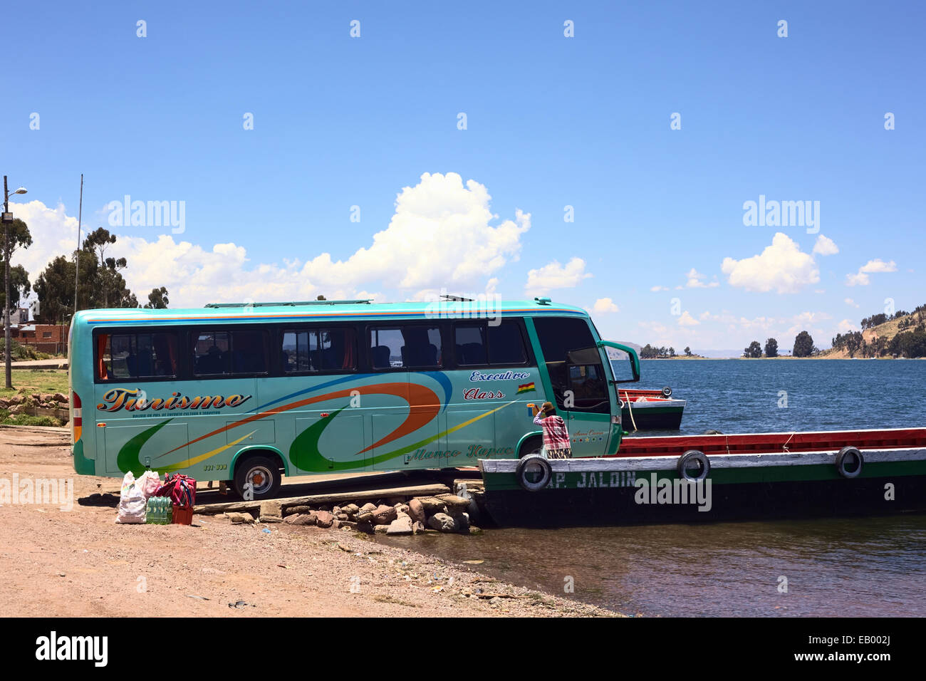 Bus leaving a wooden ferry on the shore of Lake Titicaca at