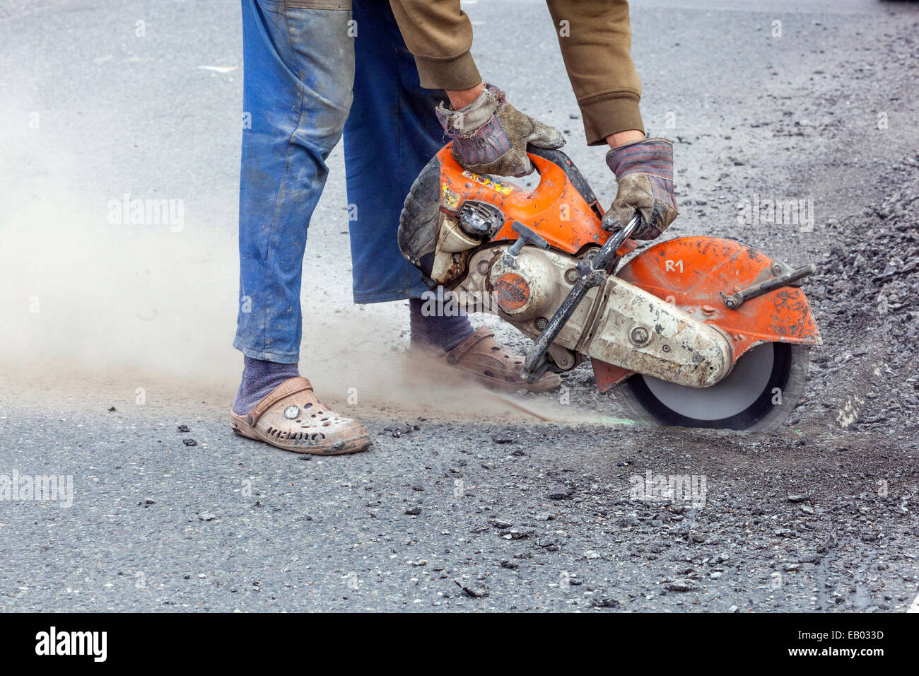 A man works cut asphalt road with a diamond cutter, No protective work gear, Czech Republic - Stock Image