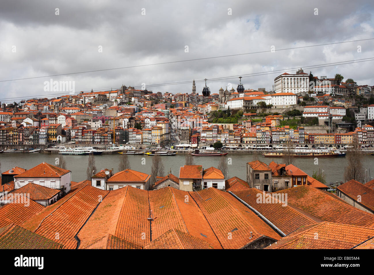 City of Porto in Portugal, view over wine cellars rooftops towards historic city centre along Douro river. Stock Photo