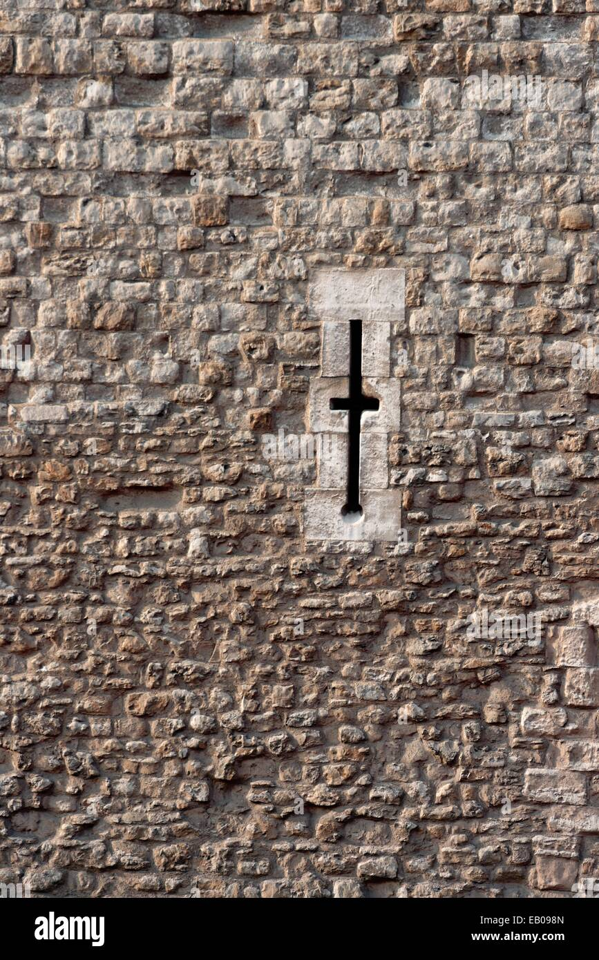 Cross shaped window in the Tower Of London used for firing down on old enemies with arrows. - Stock Image