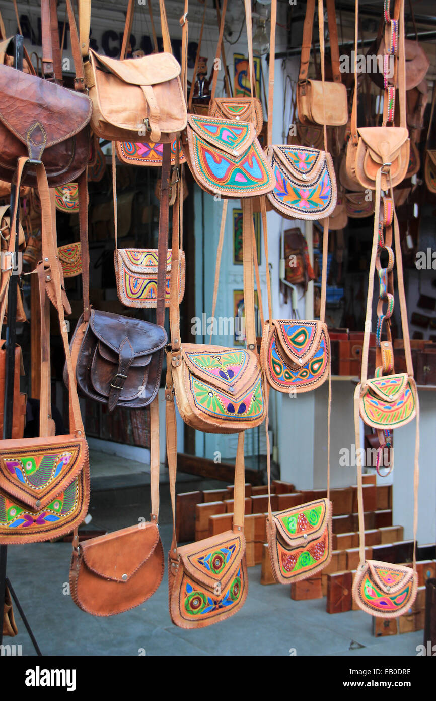 Display of colorful leather hanging purses used by ladies - Stock Image