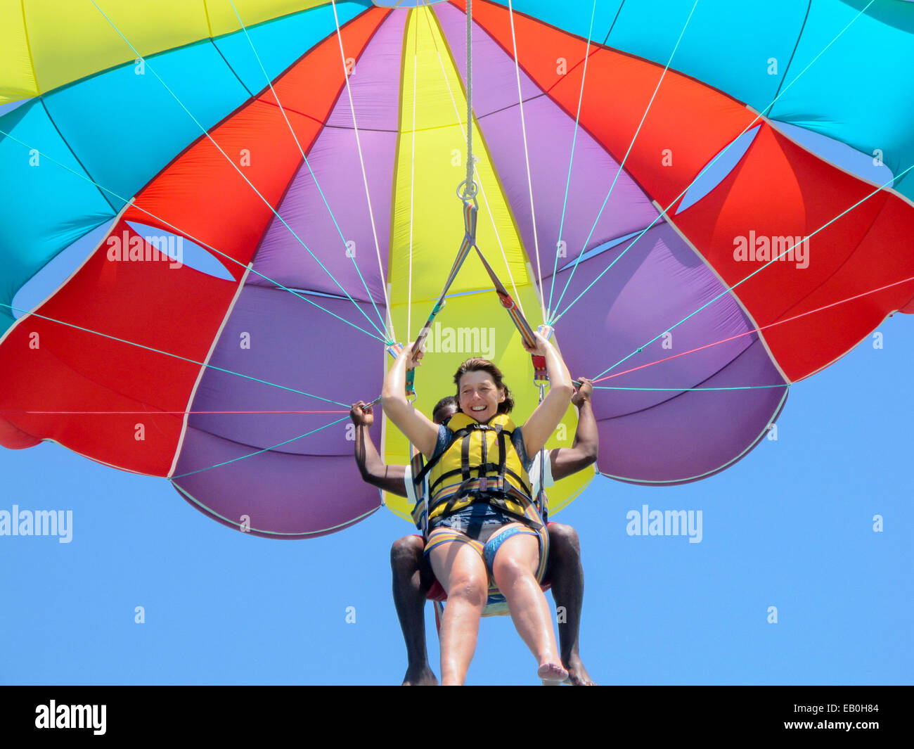A middle age woman in her 50s parasailing or parascending, with help, Mauritius - Stock Image