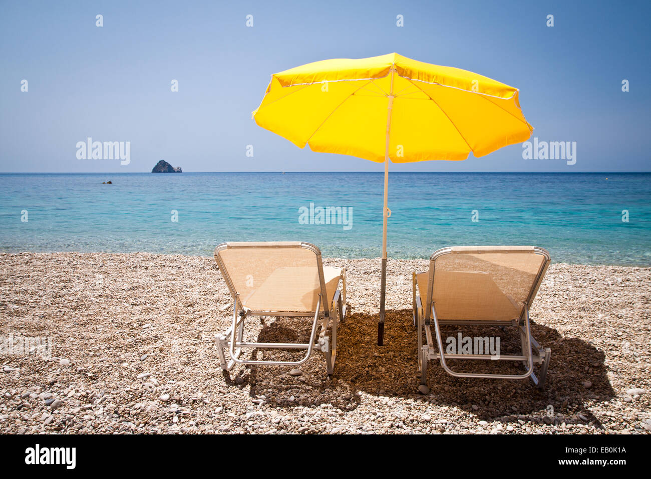Sun loungers and parasol on the beach - Stock Image